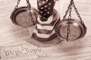 Your legal rights represented by an image of the scales of justice and the American flag and the constitution of the USA